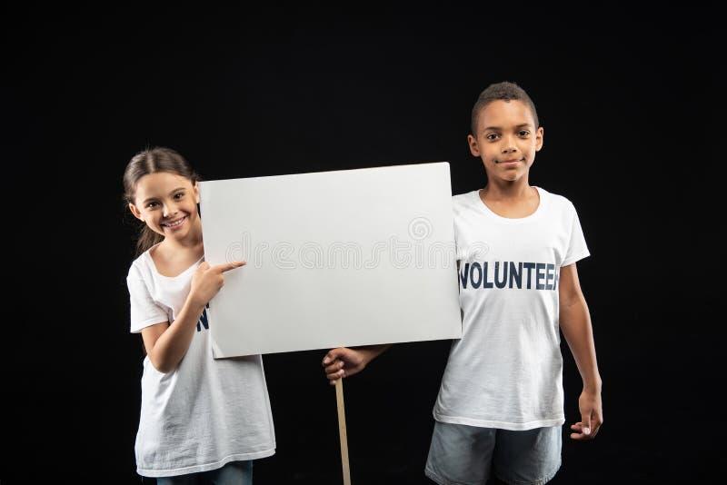 Волонтеры сигнала тревоги держа белую таблицу стоковые фото