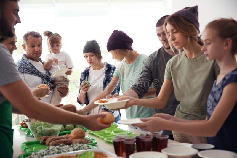 Волонтеры служа еда для бедных человеков стоковое фото rf