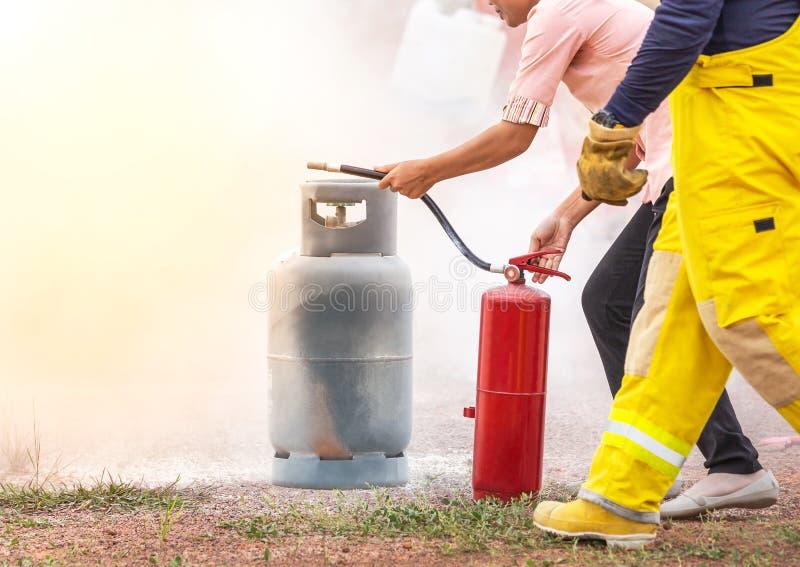 Волонтер используя огнетушитель от шланга для пожаротушения во время основной противопожарной тренировки стоковое фото rf