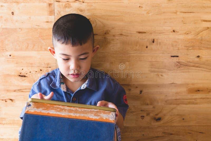 Волосы азиатского мальчика черные держа играть smartphone стоковая фотография
