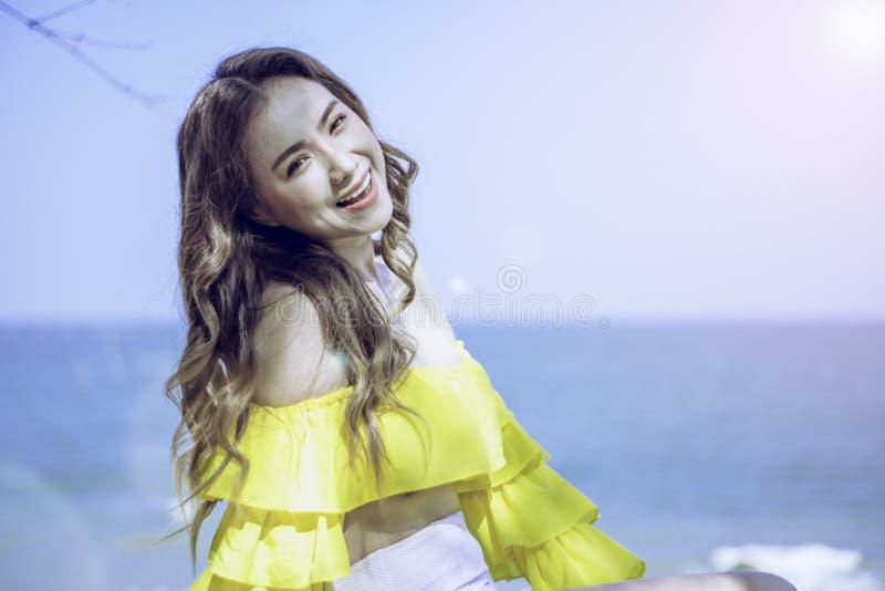 Волосы азиатской девушки портрета длинные, позиция белого и желтого, стоящего столба 2-тона бикини счастливая морем, в Таиланде Ю стоковое изображение