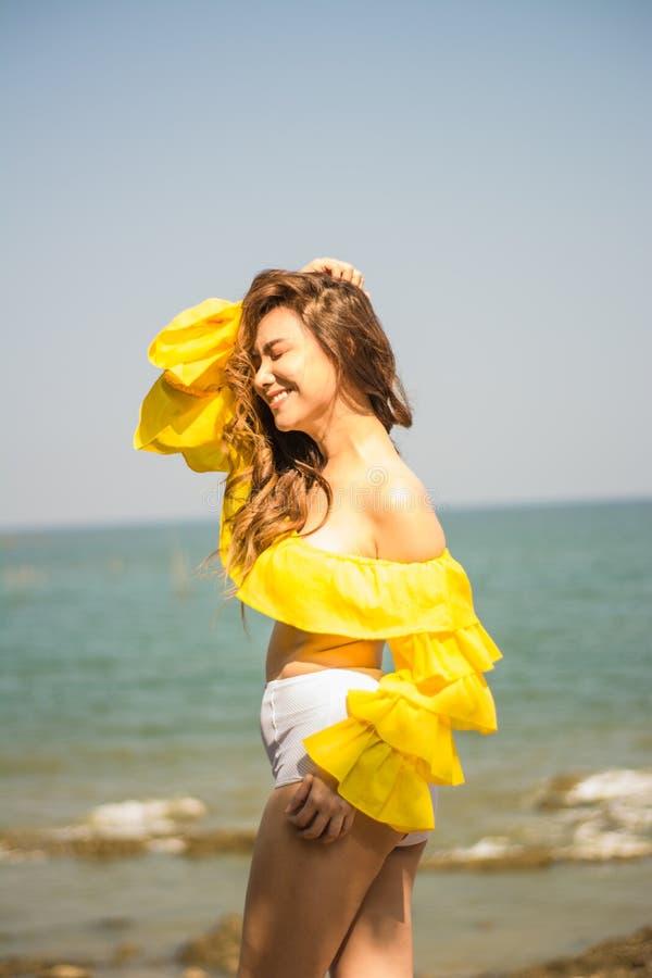 Волосы азиатской девушки портрета длинные, позиция белого и желтого, стоящего столба 2-тона бикини счастливая морем, в Таиланде Ю стоковые изображения