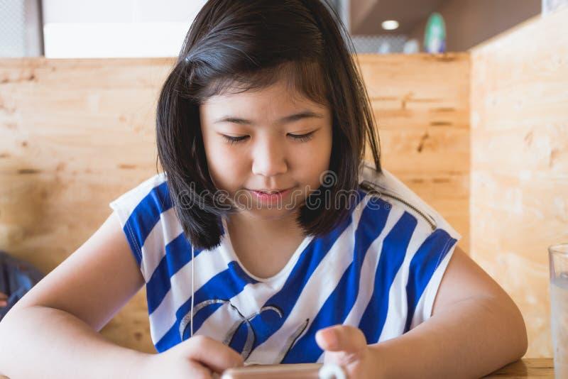 Волосы азиатской маленькой девочки черные держа играть smartphone стоковые изображения rf