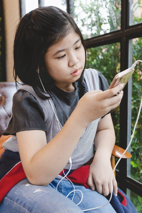 Волосы азиатской маленькой девочки черные держа играть smartphone стоковая фотография