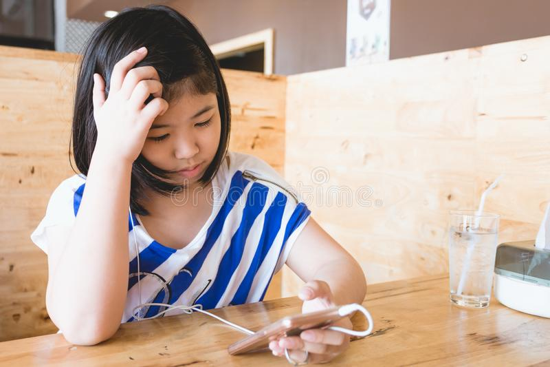 Волосы азиатской маленькой девочки черные держа играть smartphone стоковые изображения