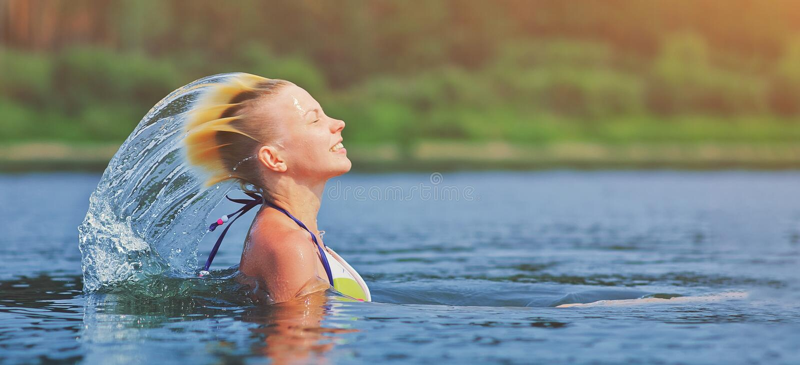 Волосы активной молодой белокурой женщины развевая брызгая воду в реке Красивая здоровая дама ослабляет и смеяться, поднимая голо стоковая фотография rf