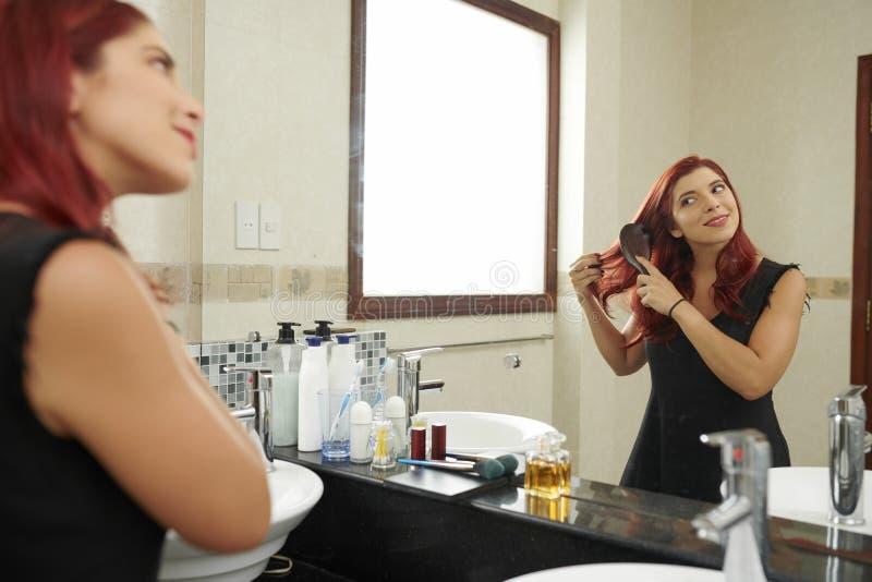 Волосы женщины чистя щеткой стоковое фото rf
