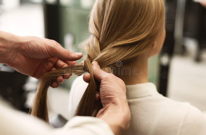 Волосы заплетая девушки стилизатора в студии красоты, крупном плане стоковая фотография