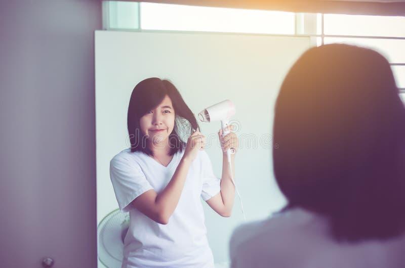 Волосы молодой азиатской женщины суша на фронте зеркала, женском сушащ ее короткие волосы с сушильщиком стоковые фото