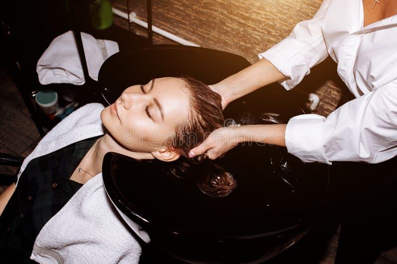 Волосы парикмахера моя к клиенту перед делать стиль причесок Парикмахер прикладывая кормя маску на волосах женщины в красоте стоковые фотографии rf