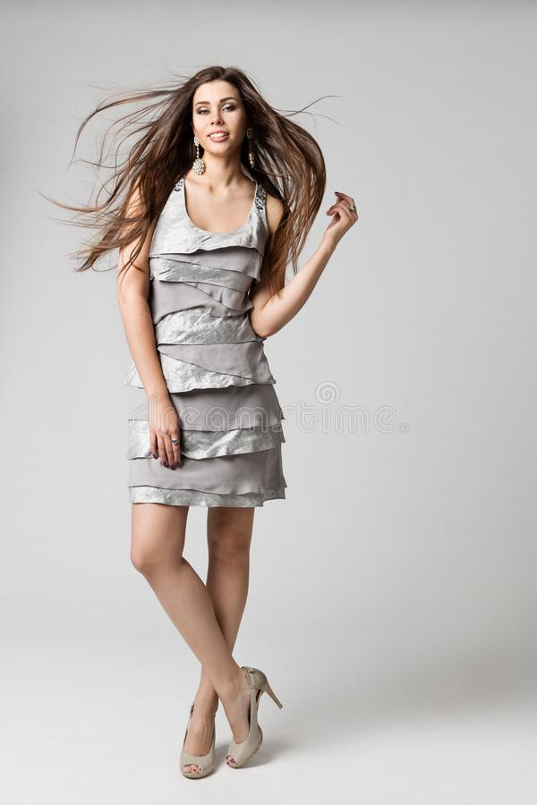 Волосы фотомодели длинные порхая на ветре, серебряном платье, портрете красоты студии женщины полнометражном на белизне стоковые фотографии rf