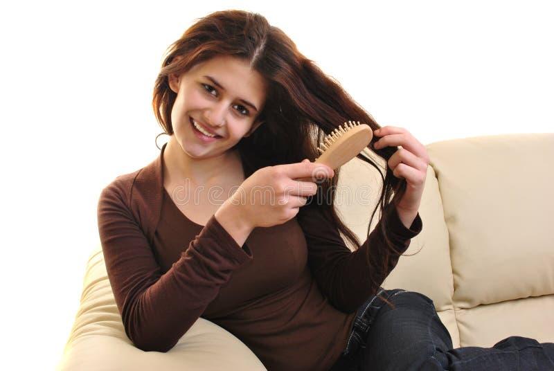 волосы щетки вручают ее детенышей женщины стоковое изображение