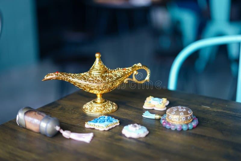 Волшебная лампа Волшебная лампа на таблице с печеньями сахара & другими аравийскими аксессуарами как бутылки песка и браслет ювел стоковое фото