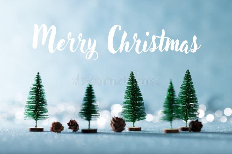 Волшебная предпосылка страны чудес зимы Миниатюрные вечнозеленые деревья и конусы сосны на сияющей голубой предпосылке с bokeh стоковое изображение