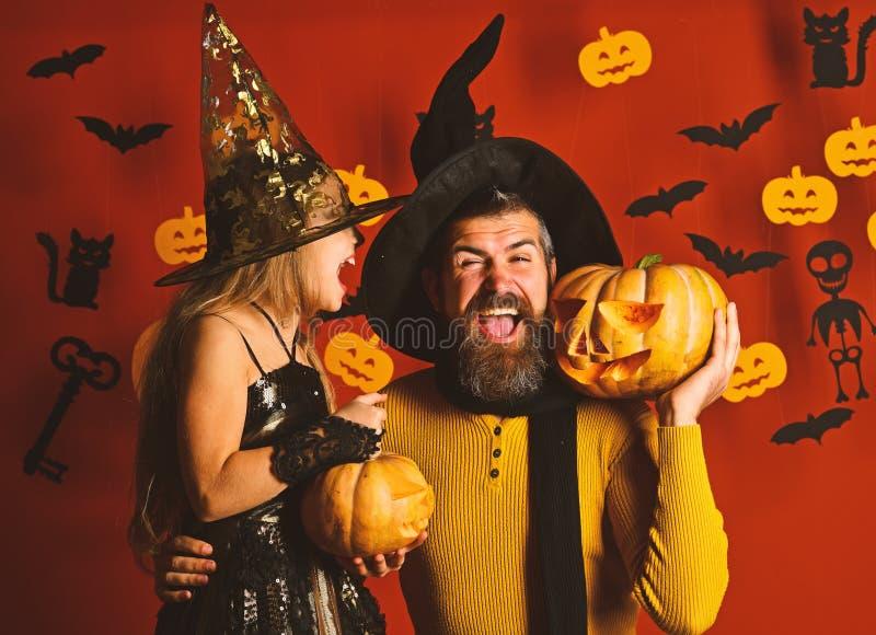 Волшебник и ведьма в черных шляпах держат тыквы стоковые изображения rf
