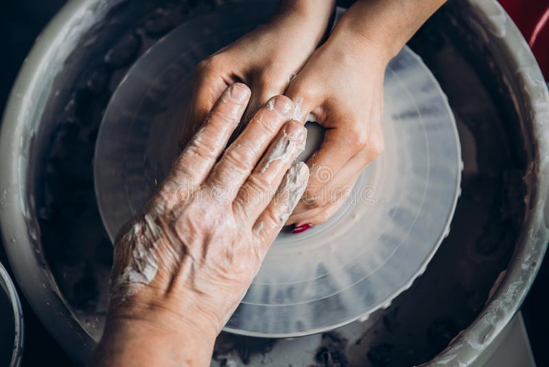 Волшебник показывает работу студента с глиной на колесе гончара, его руки в морщинках стары и молоды Концепция менторства стоковое фото