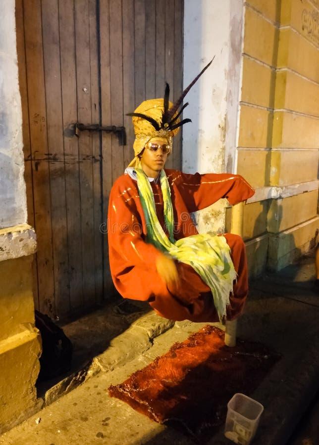 Волшебник с красивой оранжевой одеждой делая фокус левитации стоковая фотография