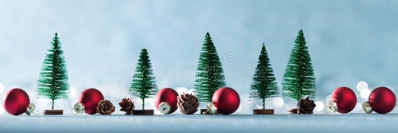 Волшебное миниатюрное знамя страны чудес зимы Вечнозеленые деревья, конусы сосны и красные безделушки рождества на сияющей голубо стоковое изображение