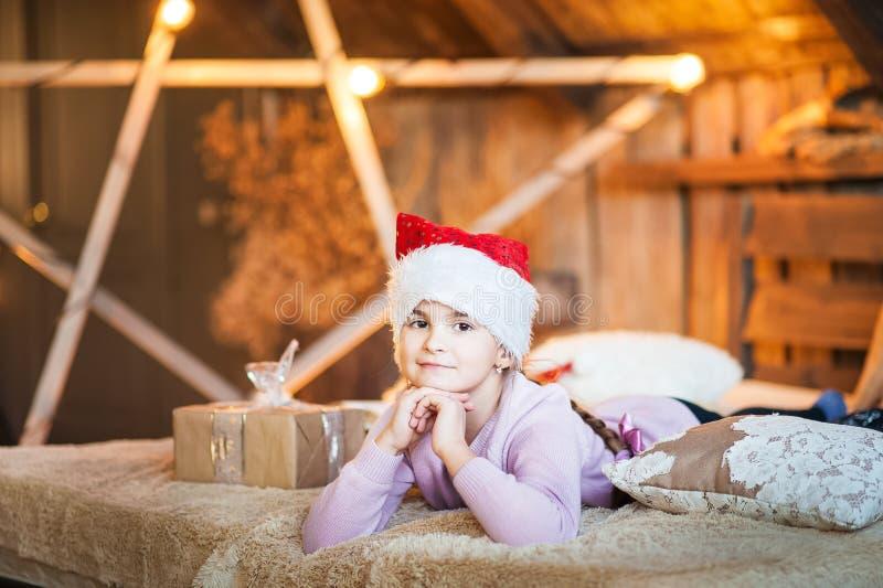 Волшебное фото маленькой девочки дома на кровати под рождеством Портрет девушки в розовом конце-вверх свитера со шляпой s стоковые изображения rf