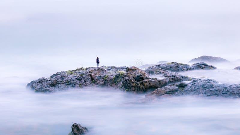 Волшебный пейзаж с одиноким человеком и сюрреалистическими камнями в море стоковая фотография