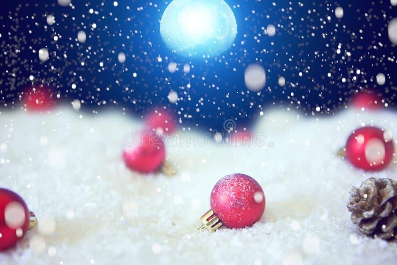 Волшебство рождества снега освещает предпосылку Рождественская открытка с лесом зимы и украшения рождества в залитой лунным свето стоковое фото rf