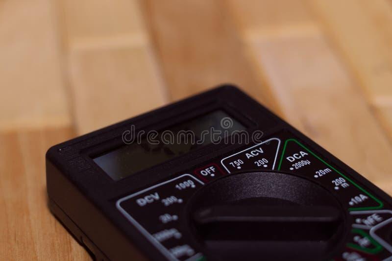 Вольтамперомметр цифров измеряя на деревянном поле Оно показывает 4 33V или польностью порученная батарея Включает вольтметр, amp стоковое изображение