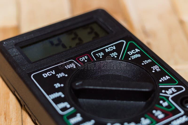 Вольтамперомметр цифров измеряя на деревянном поле Оно показывает 4 33V или польностью порученная батарея Включает вольтметр, amp стоковое фото rf