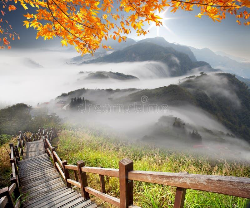 Воображение горной тропы над облаками на солнечная яркой стоковые фото