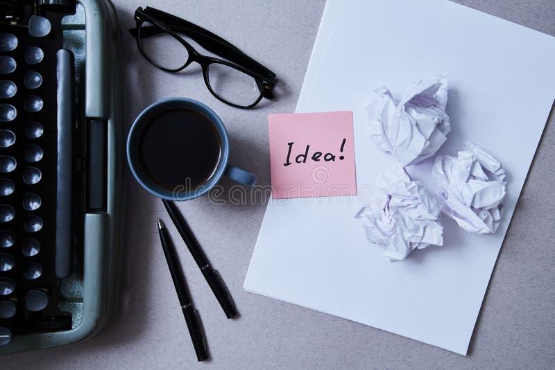 Воодушевленность, проницательность или хорошая концепция идеи: машинка, скомканная бумага вокруг чистого листа бумаги со стикером стоковые фото