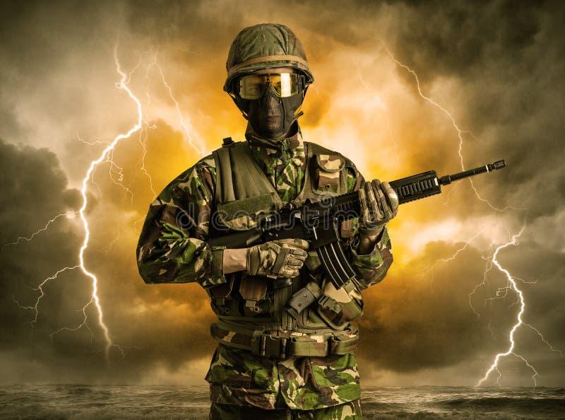 Вооруженное положение солдата в неясной погоде стоковое изображение rf