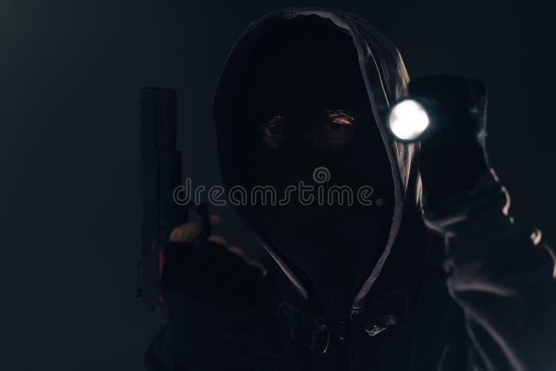 Вооруженный самолет-нарушитель взломщика с факелом электрофонаря вечером стоковая фотография