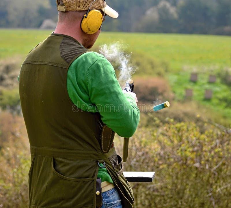 Вооруженный человек с куря корокоствольным оружием после съемки стоковые фото