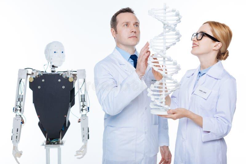 Воодушевленные необыкновенные ученые видя будущее робототехники в генах стоковая фотография rf