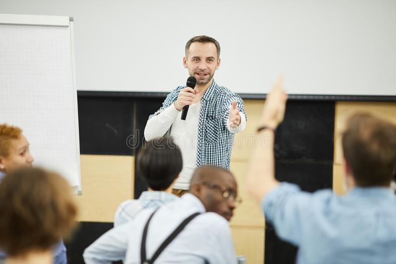 Вопрос о тренера дела отвечая от аудитории стоковое фото