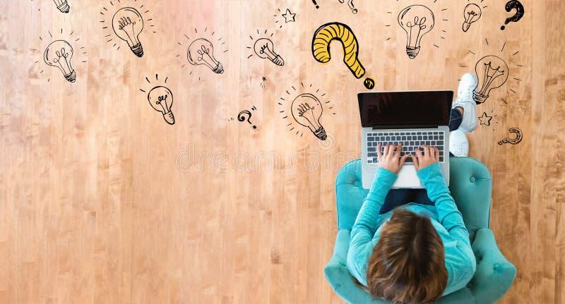 Вопрос с электрическими лампочками с женщиной используя ноутбук стоковое фото rf