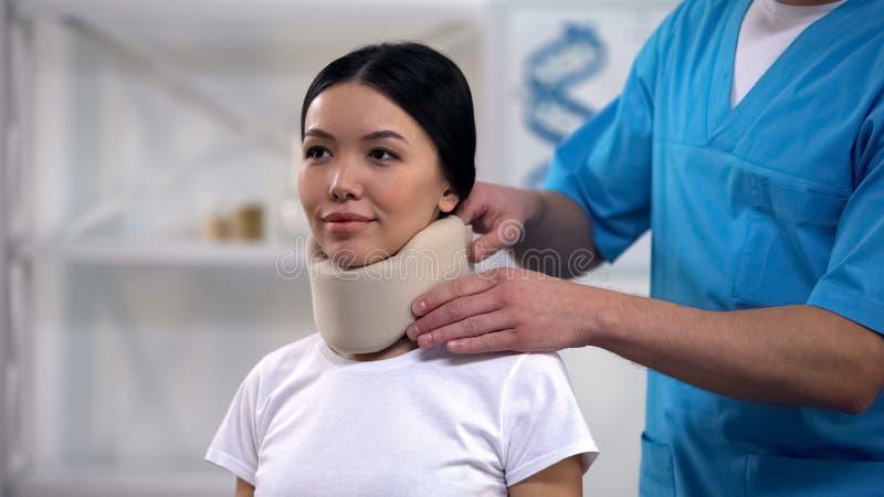 Воротник мужской пены отладки врача счастливой женской терпеливой цервикальный, реабилитация стоковая фотография rf