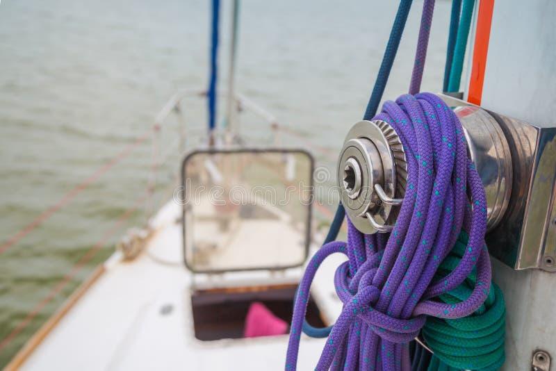 Ворот установленный на рангоуте с веревочками ранит вокруг его на фоне открытого люка перед яхтой стоковые фото