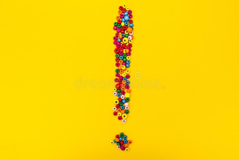 Восклицательный знак от красочных игрушек шариков на желтой предпосылке Внимание стоковая фотография