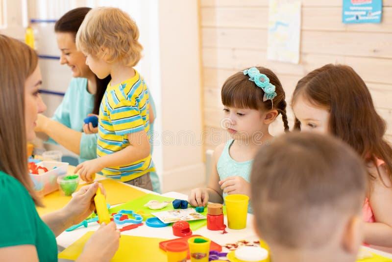 Воспитательница детского сада учит группе в составе глина моделирования детей стоковая фотография