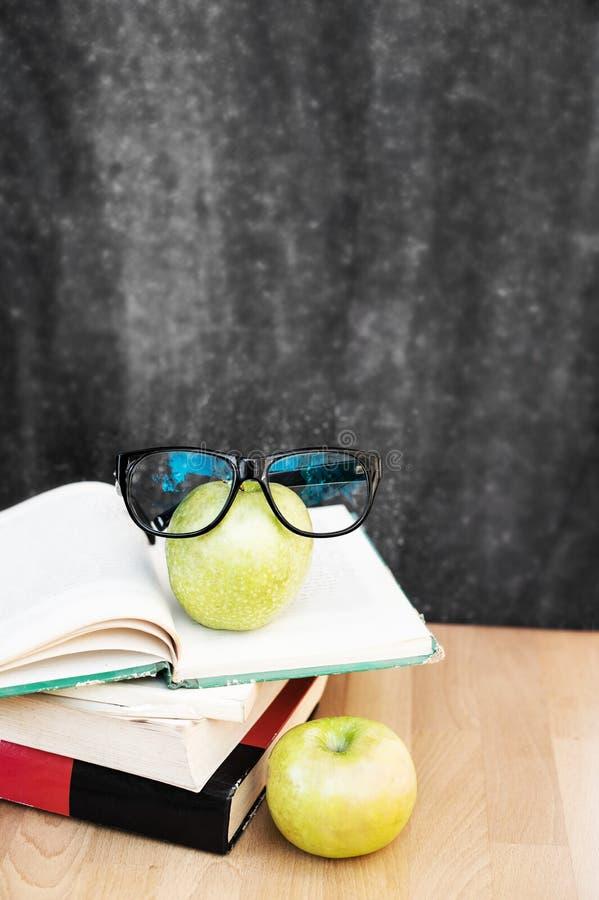 Воспитательный состав с книгами, яблоками и черным мелом стоковые фото