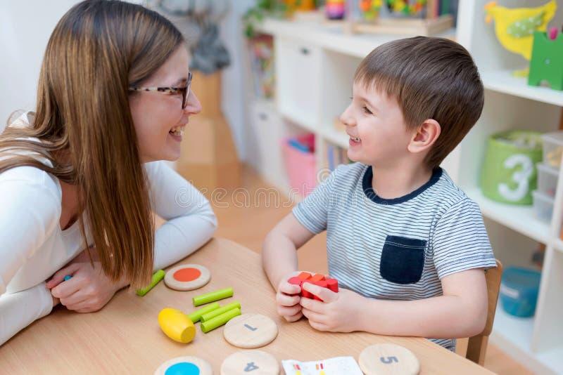 Воспитательница детского сада поддерживает милого мальчика в воспитательной игре игры стоковая фотография