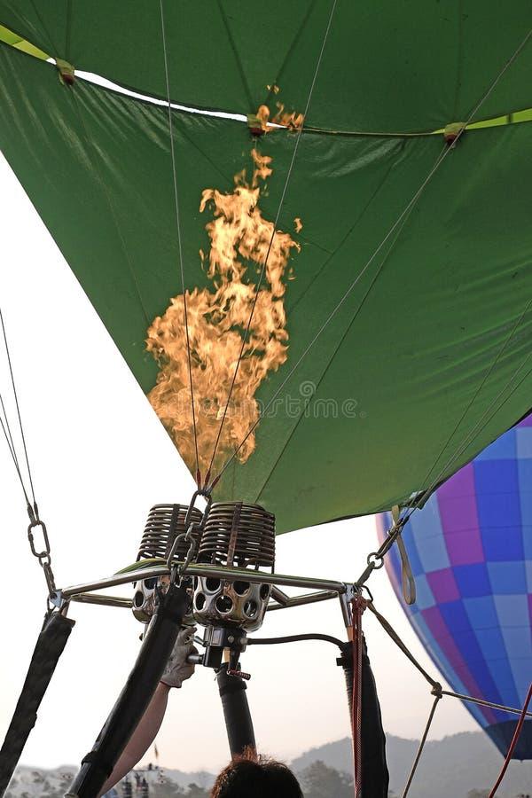 Воспламеняет огонь и надувает воздушный шар Деталь большого горячего воздушного шара будучи надуванным для своего начального поле стоковые фотографии rf