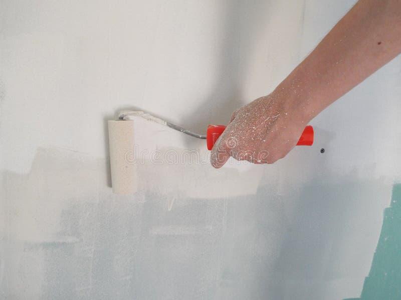 Воспламенять стены с роликом в доме стоковые фото