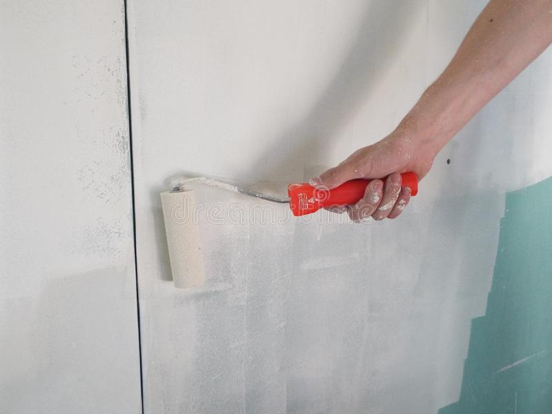 Воспламенять стены с роликом в доме стоковое фото