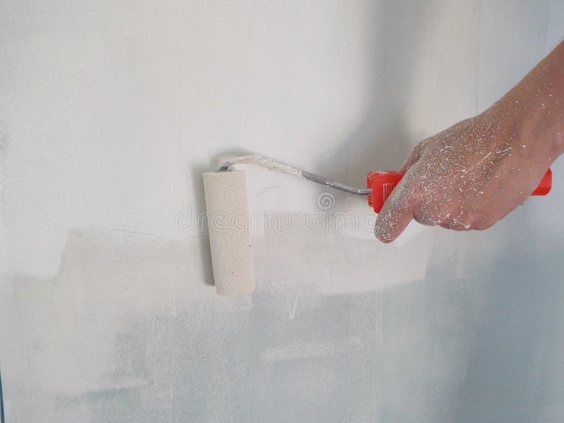 Воспламенять стены с роликом в доме стоковая фотография