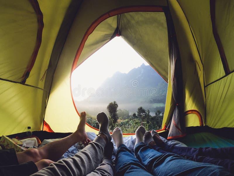 Воссоздание на горе в располагаясь лагерем шатре группа в составе ноги лежа вниз внутри шатра с горным видом в заходе солнца с др стоковое изображение rf