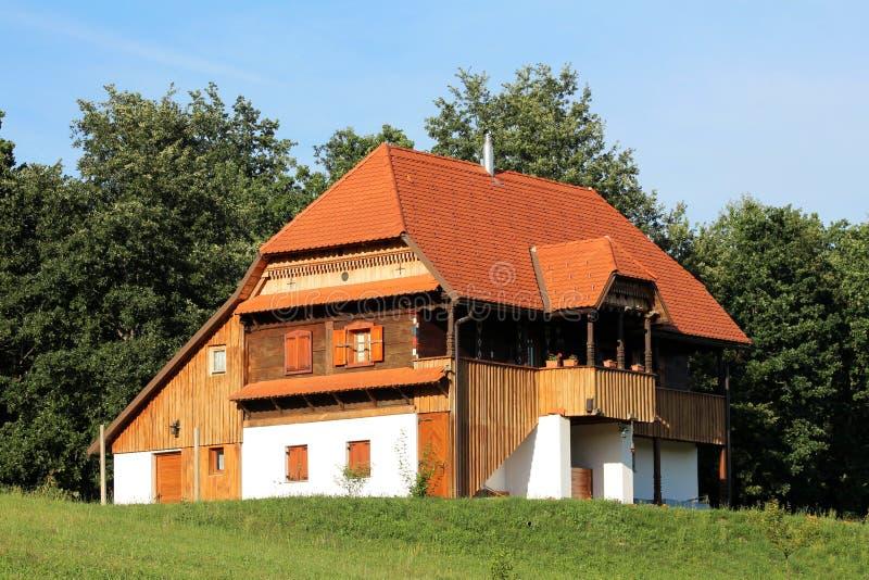 Восстановленный старый деревянный дом при украшенные детали и каменное учреждение расположенные na górze холма стоковое изображение