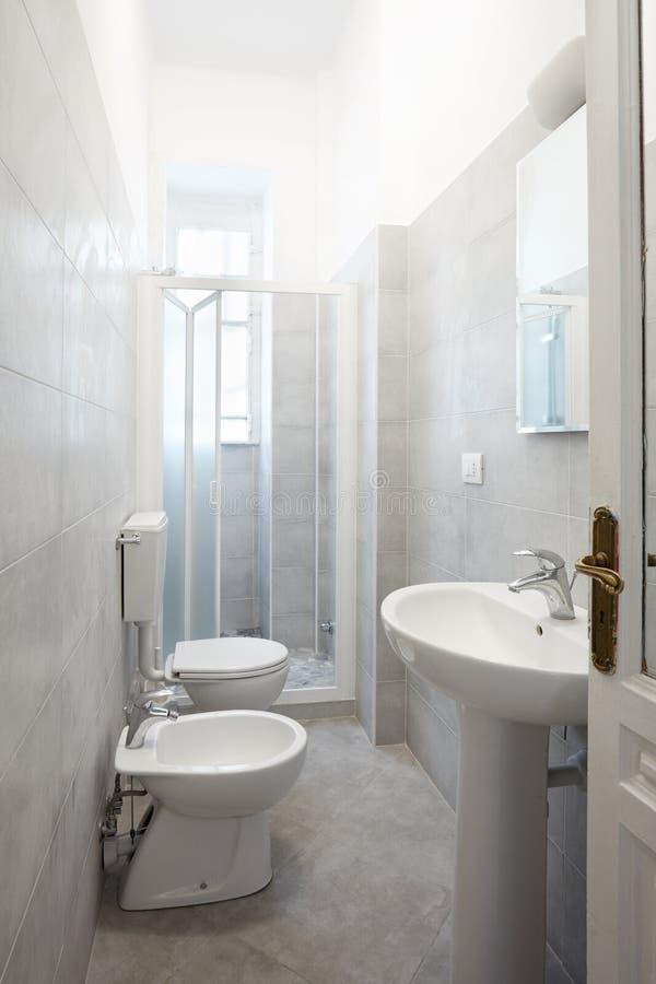 Восстановленный узкий bathroom с серыми плитками цемента стоковое изображение rf