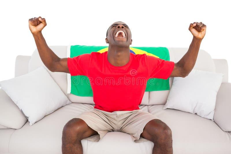 Восторженный бразильский футбольный болельщик сидя на веселить кресла стоковые изображения