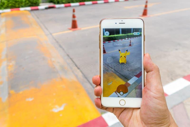 Восторженный игрок Pokemon улавливает Pikachu на улице стоковое фото